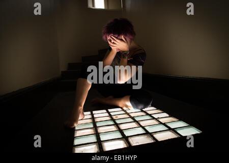 Une jeune femme désespérée adolescente dans une cellule de prison type location avec la lumière pénétrant par une Banque D'Images
