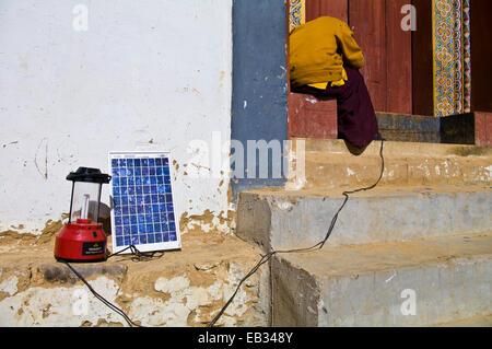 Un moine bouddhiste dans un monastère tente de réparer un panneau solaire pour recharger son téléphone cellulaire Banque D'Images