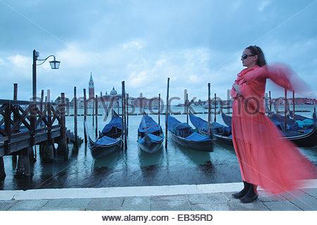 Une femme enceinte dans un fluide en robe et foulard rouge debout à côté d'amarré gondoles. Banque D'Images