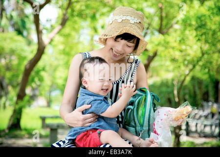 Mère avec fils (6-11 mois) in park Banque D'Images