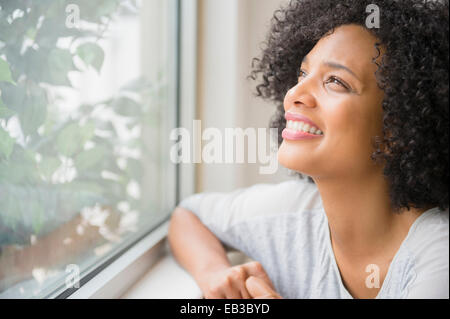 Smiling woman looking out window Banque D'Images