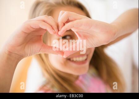 Caucasian girl faire avec les mains en forme de coeur Banque D'Images