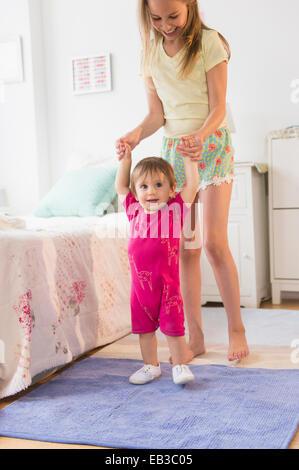 Caucasian girl aider sœur tout-petit marche dans la chambre Banque D'Images