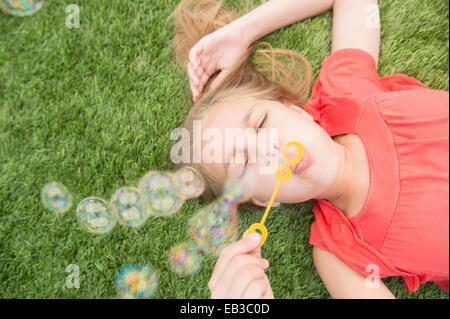 Young Girl blowing bubbles sur pelouse Banque D'Images
