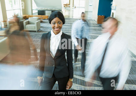 Businesswoman standing in office lobby toujours occupé Banque D'Images