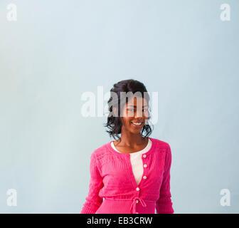 Studio portrait of mid adult woman wearing cardigan rose Banque D'Images