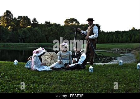 La famille victorienne avec un vélo à côté d'un étang Banque D'Images