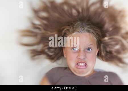 Fille avec cheveux arrangé tirant des visages drôles