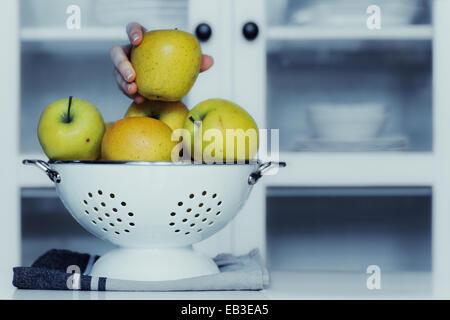 Main humaine en tenant une pomme de la passoire dans la cuisine Banque D'Images