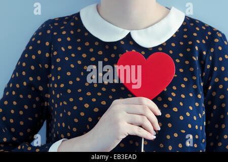 Robe à pois woman holding heart objet de forme Banque D'Images