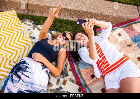 Caucasian teenage girls portant sur des couvertures de pique-nique dans le parc Banque D'Images
