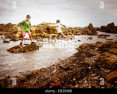 Mixed Race brother and sister playing on Rocky beach Banque D'Images