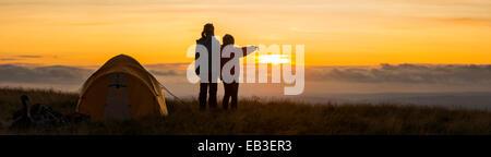 Silhouette de randonneurs surplombant au coucher du soleil à distance Banque D'Images