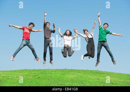 L'été, vacances, congés, les gens heureux concept - groupe d'amis de sauter sur le parc Banque D'Images