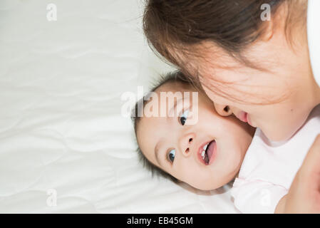 Happy happy family. Asian mother and baby kissing, rire et s'étreindre Banque D'Images