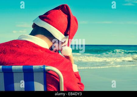 Le père noël de prendre une sieste dans une chaise de plage sur la plage Banque D'Images