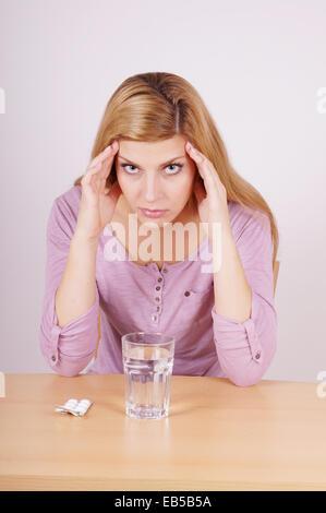 Jeune femme souffrant de maux de tête avec verre d'eau et tablettes Banque D'Images