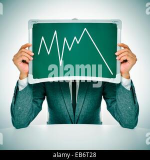 Homme portant un costume assis dans un tableau montrant un graphique des pertes économiques Banque D'Images