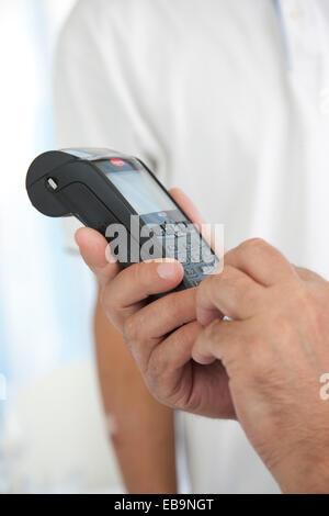Les mains de l'homme entrant dans la machine de carte de crédit Banque D'Images