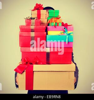 Un jeune homme en costume portant un tas de boîtes-cadeaux de différentes couleurs, avec un effet de filtre Banque D'Images
