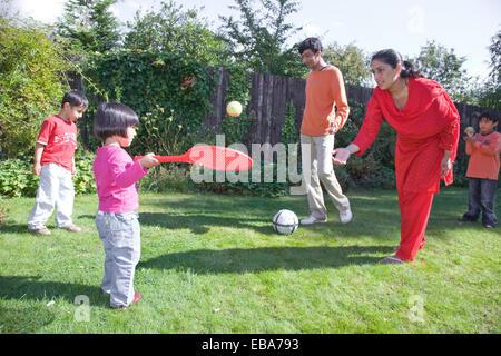 Jeune famille à jouer avec une raquette et balle dans le jardin, Banque D'Images
