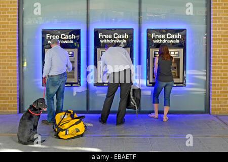 Chien avec vue arrière avec propriétaire et deux autres personnes utilisant des distributeurs automatiques de billets à la gare Kings Cross gare Camden Londres Angleterre Royaume-Uni