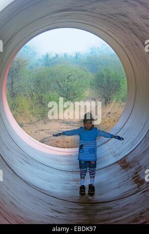 Petite fille dans un énorme tuyau, Pune, Maharashtra, Inde Banque D'Images