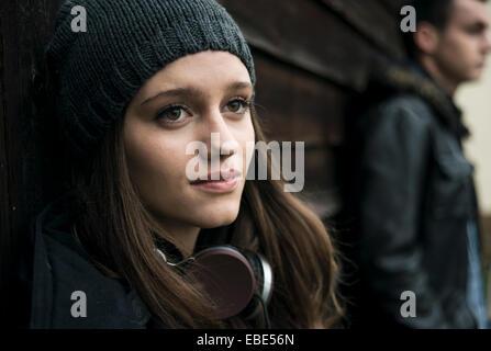 Close-up portrait of teenage girl wearing hat à l'extérieur, et les écouteurs autour du cou, avec jeune homme en Banque D'Images