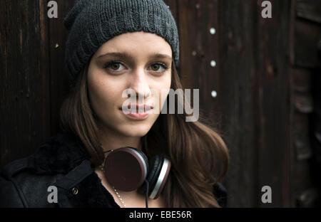 Close-up portrait of teenage girl wearing hat à l'extérieur, et les écouteurs autour du cou, looking at camera and Banque D'Images