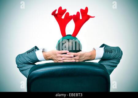 Un homme avec un bandeau reindeer antlers se détendre dans son bureau de président après un party de Noël de bureau