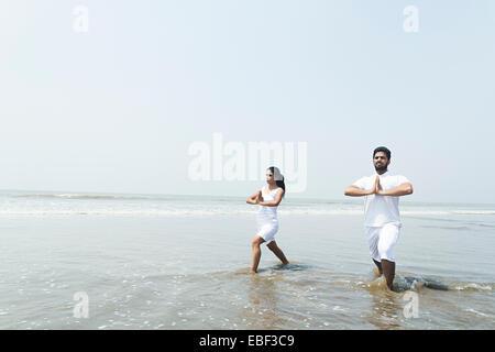 Couple indien Yoga plage Banque D'Images
