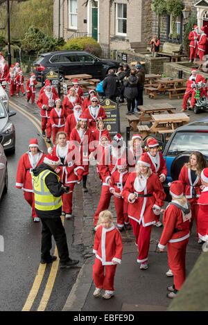 Les personnes (hommes, femmes et enfants) vêtus de rouge et blanc Père Noël tenues sont la marche, le jogging, la Banque D'Images