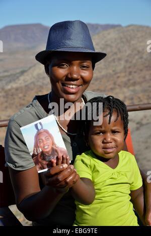 Femme Himba moderne tenant son enfant avec une photo d'elle portant des vêtements traditionnels, Orupembe, Kaokoland, Kunene, Namibie