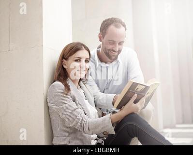 Femme appuyée contre un mur et la lecture d'un livre, l'homme à son livre, curieusement en Innsbruck, Tyrol, Autriche Banque D'Images