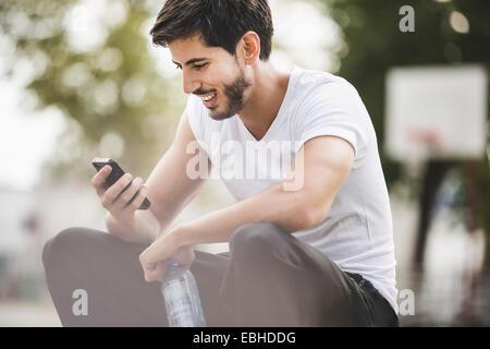 Jeune homme basket-ball la lecture de textes sur le smartphone. Banque D'Images