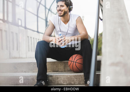 Jeune joueur de basket-ball masculin assis sur passerelle listening to headphones Banque D'Images