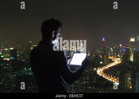 La silhouette du jeune businessman looking at digital tablet en face de la fenêtre bureau gratte-ciel dans la nuit, Shanghai, Chine