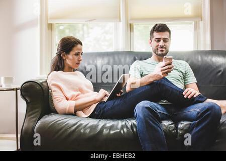 Couple et smartphone sur canapé Banque D'Images