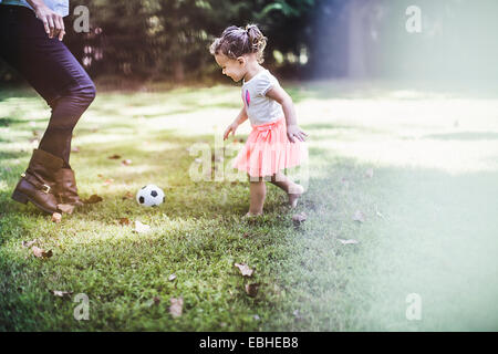 Baby Girl playing ball in garden Banque D'Images