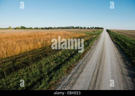 High angle view of rural road entre les champs vides Banque D'Images