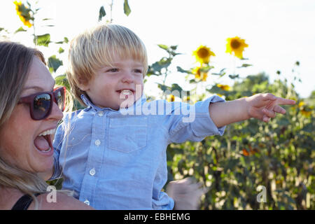 Mid adult woman and toddler fils pointant dans champ de tournesol Banque D'Images