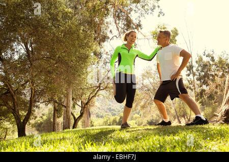 Couple mature exécutant l'échauffement dans le parc Banque D'Images