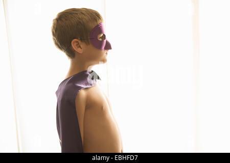 Garçon à Cape et masque à la maison Banque D'Images