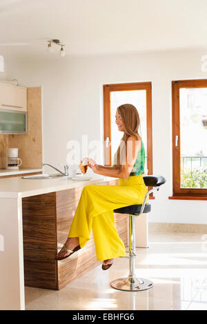 Young woman eating breakfast au comptoir de la cuisine Banque D'Images