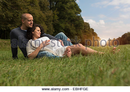Pregnant couple sitting on grass in park Banque D'Images