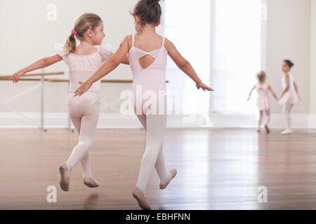 Vue arrière des filles pratiquer saut dans ballet school Banque D'Images