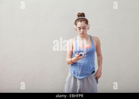 Adolescente à l'écoute de la musique dans l'école de ballet de smartphone Banque D'Images