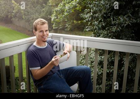 Jeune homme ayant balcon sur salade