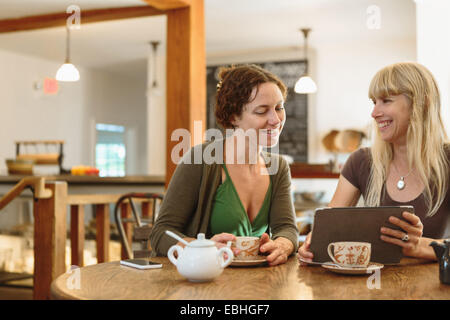 Deux amis female looking at digital tablet in country store cafe Banque D'Images