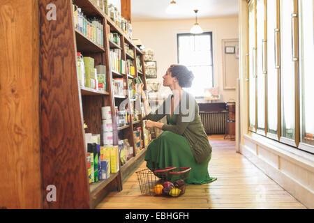 Femme accroupie à la clientèle tout en shopping in country store Banque D'Images